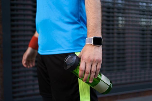 Desportista, caminhando e segurando a garrafa de esporte na mão