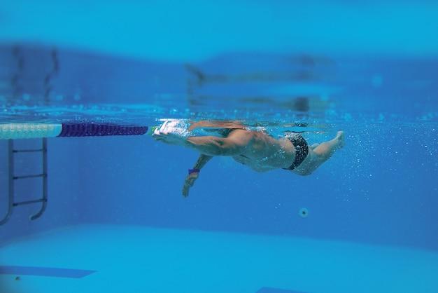 Desportista caucasiano a nadar com omoplatas para nadar na piscina debaixo de água