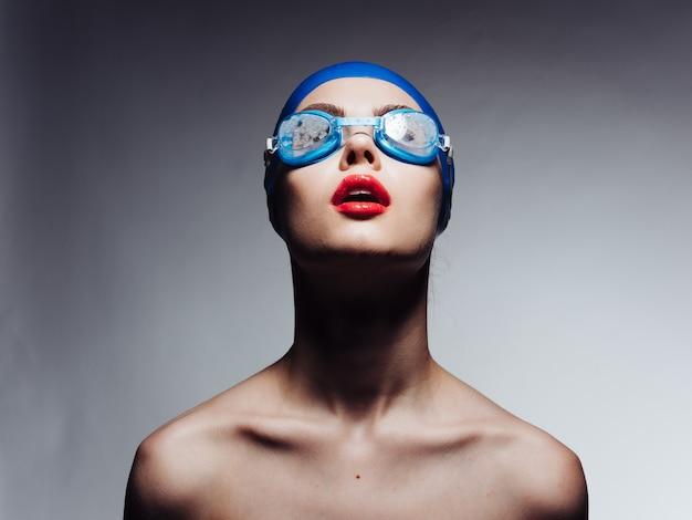 Desportista com lábios vermelhos, com uma touca de natação azul e óculos, olhando para cima vista recortada