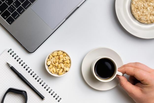 Desportista comendo arroz crocante rodadas com amendoim, xícara de café perto do laptop