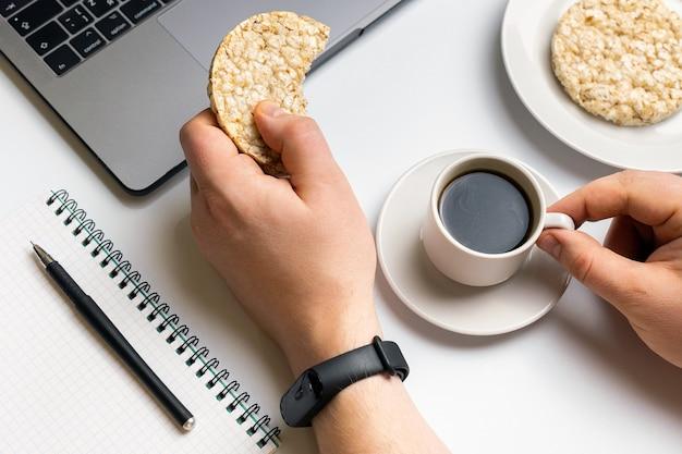 Desportista comendo arroz crocante rodadas com café perto do laptop e notebook.