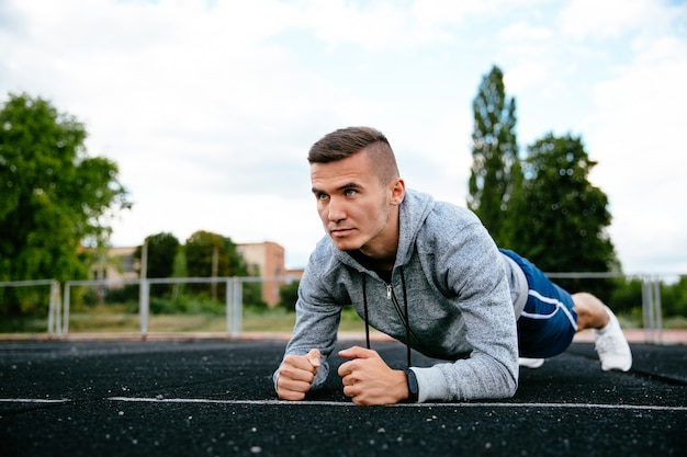 Desportista concentrada fazendo pose de prancha, exercício, malhando, vestida de jaqueta esporte cinza