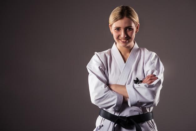 Desportista de caratê loira linda jovem em um quimono se posiciona para começar o treino.