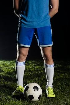 Desportista de colheita perto de bola de futebol
