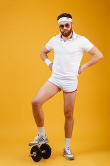 Desportista de imagem vertical em pé no haltere segurando os braços no quadril