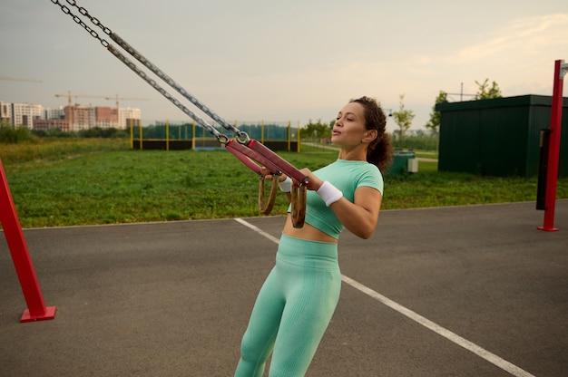 Desportista de meia idade, atleta feminina, exercício ao ar livre, malhando com cintas de fitness de suspensão estacionária no recinto desportivo ao ar livre. conceito de perda de peso, condicionamento físico, esporte e cuidados com o corpo