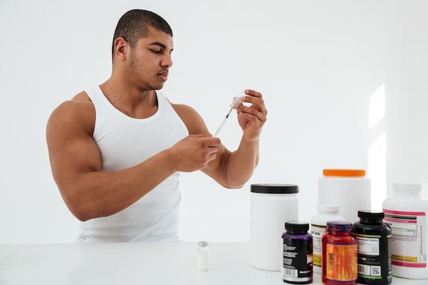 Desportista em pé sobre a parede branca, segurando a seringa