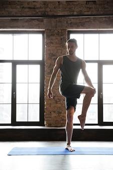 Desportista, esticar os músculos das pernas em pé no tapete