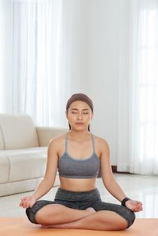 Desportista étnica, meditando em casa