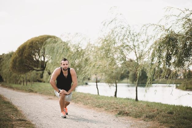 Desportista faz exercícios na rua. atleta cansado em roupas esportivas faz uma pausa.