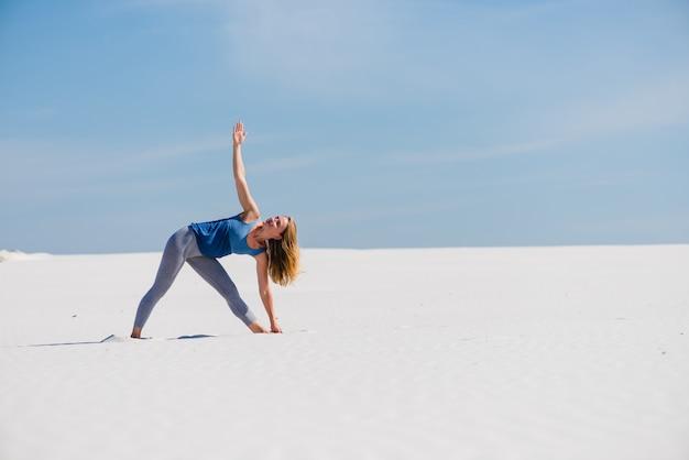 Desportista faz triângulo yoga pose ao ar livre