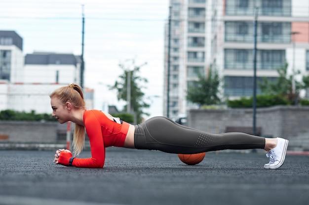 Desportista, fazendo a perna esticando o exercício com bola medicinal. cabe a mulher exercitar com bola no treino de ginásio.