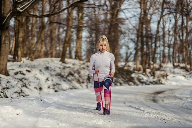 Desportista fazendo estocadas com borracha de poder em pé na natureza em um dia de inverno nevado. vida saudável, fitness de inverno, fitness ao ar livre