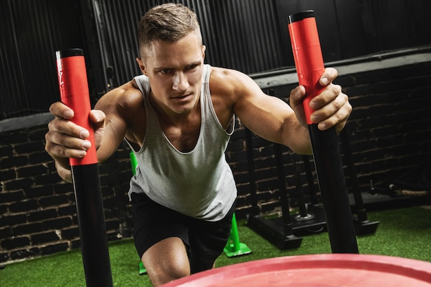 Desportista forte durante o exercício de trenó