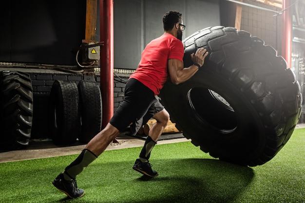 Desportista forte fazendo um exercício de flip de pneu