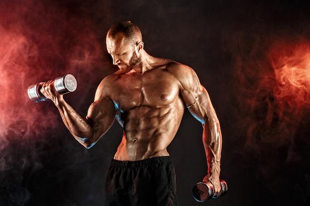 Desportista forte levantando halteres pesados em fumaça