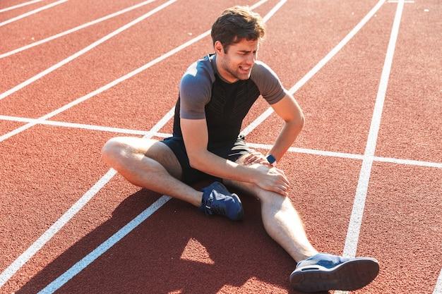 Desportista forte que sofre de uma dor no joelho