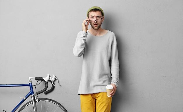 Desportista inteligente, olhando através de grandes óculos com expressão séria, tomando um delicioso café quente, indo a competições ou no ginásio.