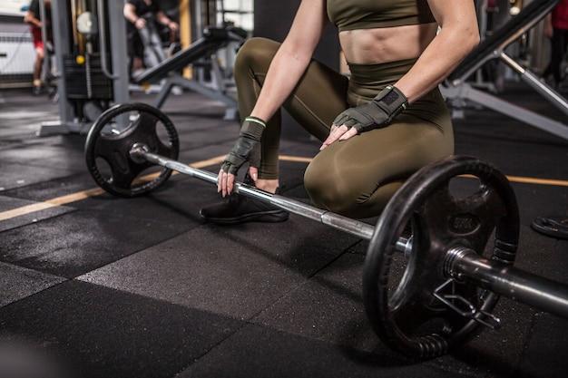 Desportista irreconhecível com corpo em forma a descansar durante um treino com barra no ginásio