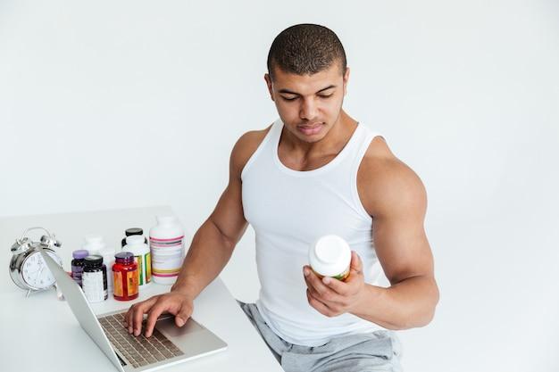 Desportista jovem bonito, segurando a nutrição do esporte e usando o computador portátil