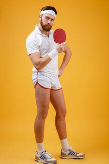 Desportista jovem bonito, segurando a raquete para tênis de mesa