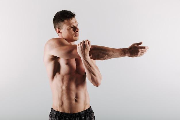 Desportista jovem concentrado bonito fazer exercícios de alongamento