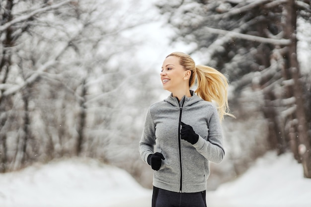 Desportista loira correndo na floresta em dia de inverno nevado. fitness de inverno, esporte, hábitos saudáveis