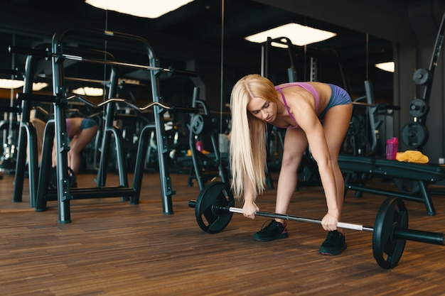 Desportista loira em mini shorts, levantando a barra no treino de ginásio