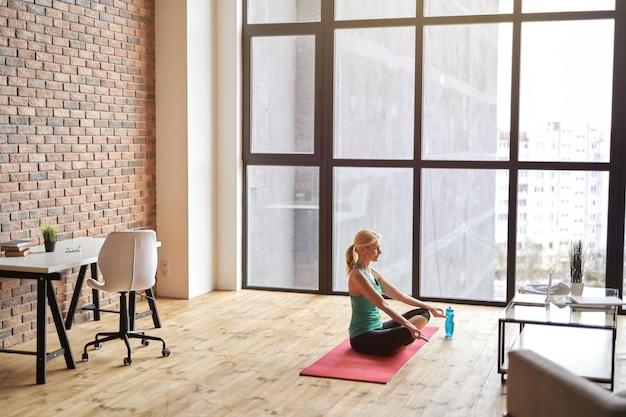 Desportista madura sentada em posição de lótus em um tapete e usando o laptop enquanto pratica ioga em casa em