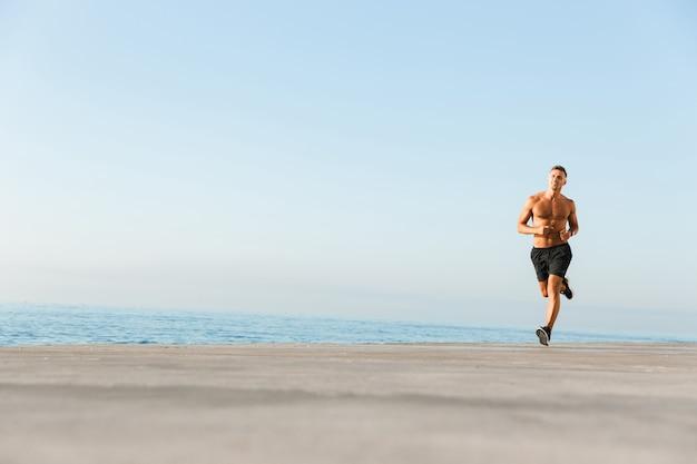 Desportista maduro correndo na praia ao ar livre.