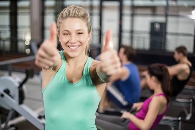 Desportista mostrando os polegares no ginásio