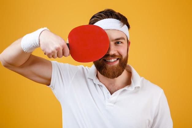 Desportista novo alegre que guarda a raquete para o tênis de mesa.
