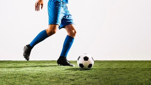 Desportista, preparando-se para chutar a bola