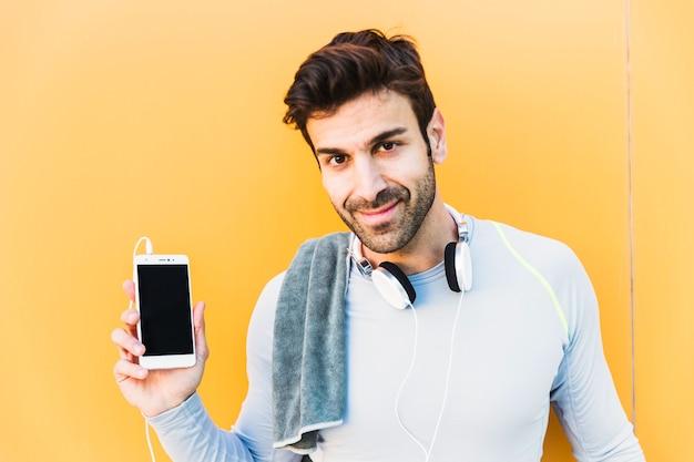 Desportista que demonstra o smartphone