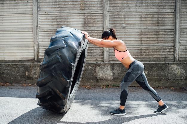 Desportista que treina a roda de levantamento de peso ao ar livre
