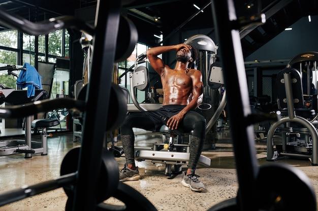 Desportista sem camisa cansada, descansando na máquina de ginástica