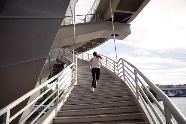 Desportista subindo as escadas ao pôr do sol