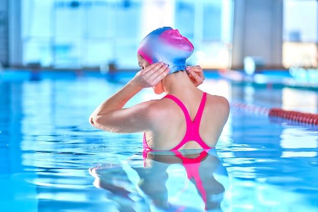 Desportiva cabe mulher em natação chapéu e maiô aprende a nadar na piscina de esportes no centro de lazer