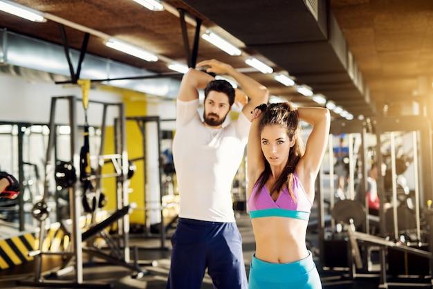 Desportiva jovem atlética fazendo alongamento de braços no ginásio moderno na frente do forte treinador pessoal musculoso.