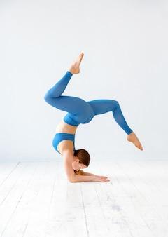 Desportiva jovem fazendo um suporte de cotovelo pose de ioga com as pernas espalhadas em um ginásio de alta chave