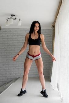Desportiva jovem posando no estúdio sobre um fundo claro. fitness, estilo de vida saudável.