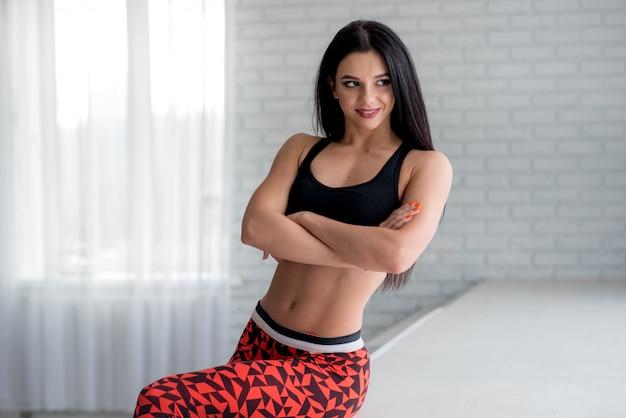 Desportiva jovem posando no estúdio sobre um fundo claro. fitness, estilo de vida saudável