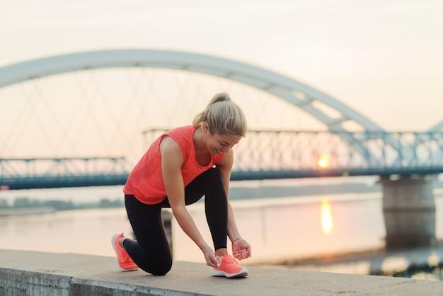 Desportiva linda garota loira amarrando o cadarço antes de treinar fora. linda loira desportiva esticando seus músculos após treinamento duro lá fora.
