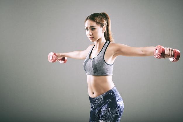 Desportiva menina asiática fazendo aumento lateral com halteres