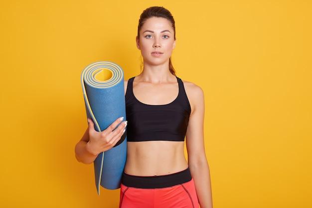 Desportiva menina segurando o tapete de ioga nas mãos, vestindo calças e sutiã preto