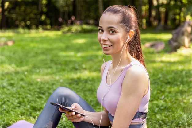 Desportiva menina sentada em um tapete de ioga e ouvir música