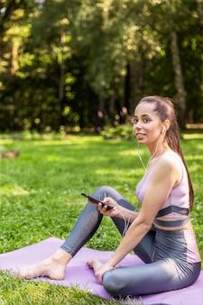 Desportiva menina sentada em um tapete de ioga ouve uma música no parque