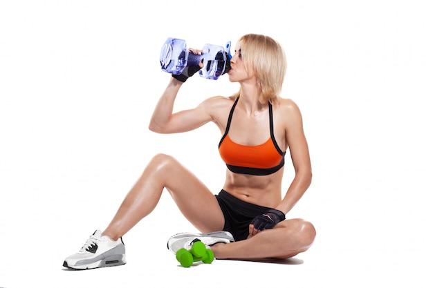 Desportiva menina sentada no chão, bebendo água