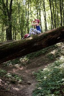 Desportiva menina sentada no tronco na floresta e beber água de uma garrafa