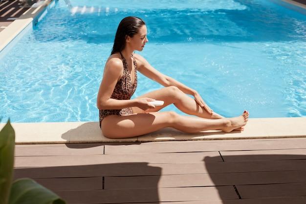 Desportiva morena relaxada sentada perto da piscina no chão de madeira, aplicar creme de banhos de sol com cuidado, segurando o tubo branco em uma mão